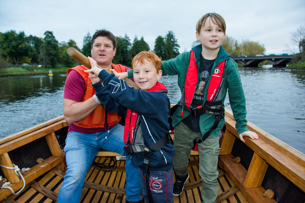 Lagan Currachs team member Tim shows young boys how to steer a currach on the River Lagan, Belfast - photo 9245. Featured image.